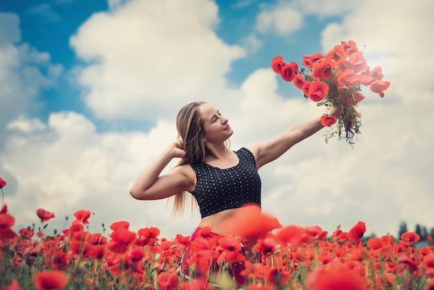 Ukrainisches mädchen in der sportbekleidung, die einen blumenstrauß von mohnblumen im feld, sommerzeit hält