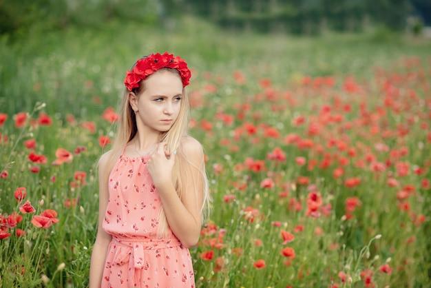 Ukrainisches schönes mädchen auf dem gebiet der mohnblumen und des weizens.