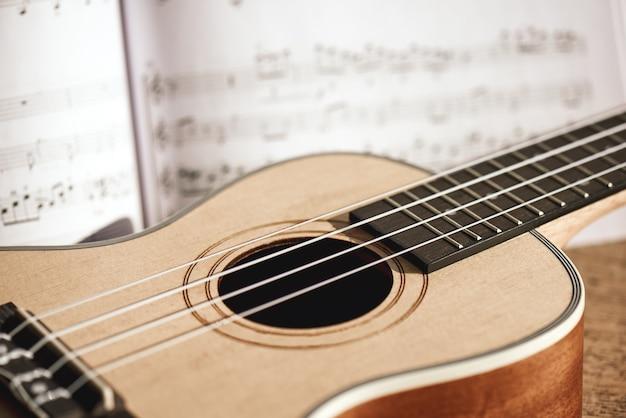 Ukulele akkorde. nahaufnahmefoto der ukulele-gitarre und der musiknoten gegen den hölzernen hintergrund. musikinstrumente. musikequipment