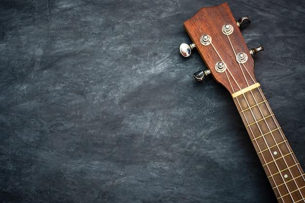 Ukulele auf schwarzem zement. konzept der hawaiianischen musikinstrumente und musikliebhaber.