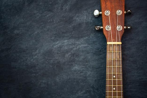 Ukulele auf schwarzem zement. spindelstock und bund der ukuleleteile.