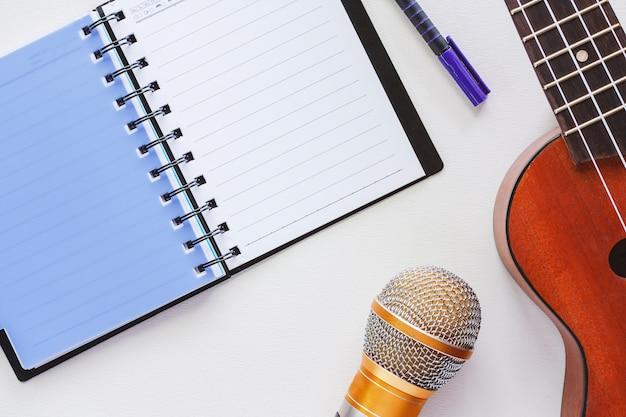Ukulele mit geöffnetem gewundenem notizbuch, stift und mikrofon auf weißem hintergrund