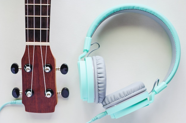 Ukulele mit grünen kopfhörern auf weißem hintergrund für musikinstrument