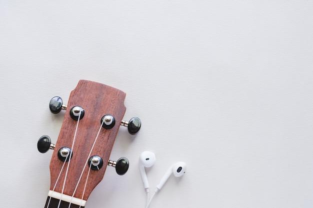 Ukulele mit kopfhörern auf weißem hintergrund