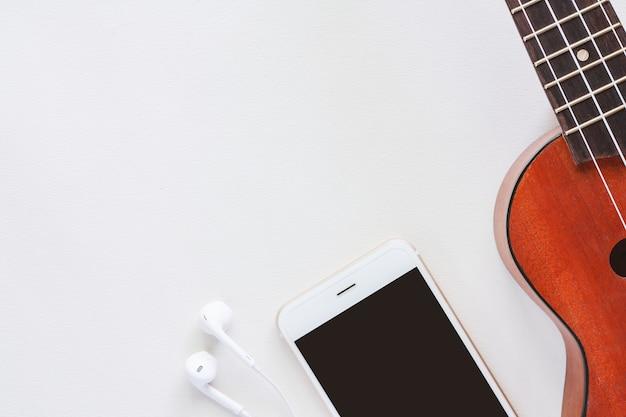 Ukulele mit smartphone und kopfhörern auf weißem hintergrund