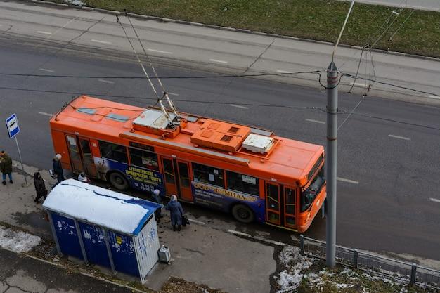 Uljanowsk, russland - 03. dezember 2019: moderner elektrischer oberleitungsbus, der am sonnigen wintertag von der haltestelle der öffentlichen verkehrsmittel abfährt. umweltfreundlicher transport.