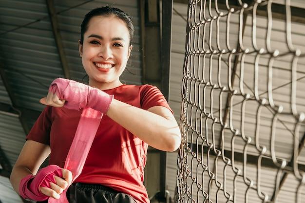 Ultimative asiatische kämpferin, die sich fertig macht, lächelnde muskulöse asiatische kämpferin mit rotem riemen am handgelenk