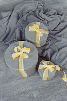 Ultimative graue runde geschenkboxen, die gelbe schleife beleuchten