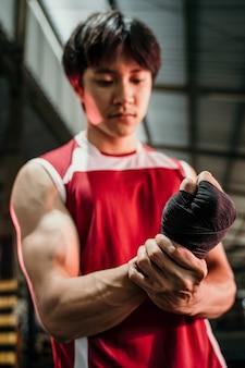 Ultimativer asiatischer kämpfer, der sich fertig macht, muskulöser asiatischer kämpfer mit schwarzem riemen am handgelenk