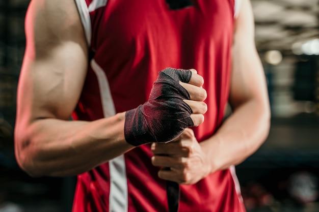 Ultimativer kämpfer, der sich fertig macht, muskulöser boxer mit schwarzem riemen am handgelenk