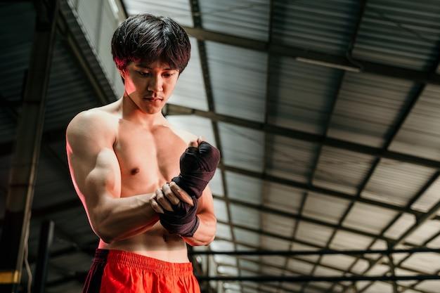 Ultimativer kämpfer, der sich fertig macht, muskulöser kämpfer mit schwarzem riemen am handgelenk