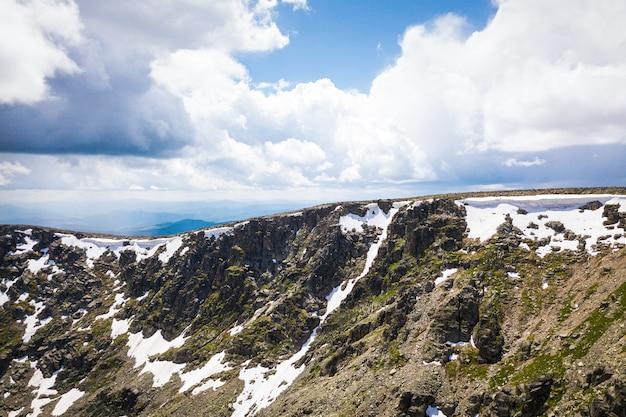 Ultraweites panorama über den horizont. berge mit schnee bedeckt, lichtung mit einem grünen nadelwald gegen den blauen himmel.
