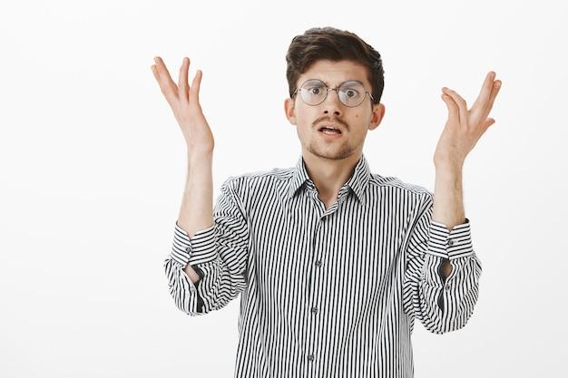 Um gottes willen warum. porträt eines genervten, intensiven, attraktiven europäischen it-managers in einer brille, der handflächen hebt und nervös die hände schüttelt, schockiert und unzufrieden mit dem dummen fehler eines kollegen