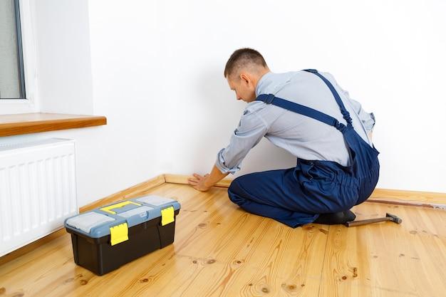 Um reparaturen vorzunehmen. anbringen einer neuen sockelleiste. ein mann macht reparaturen in einem zimmer