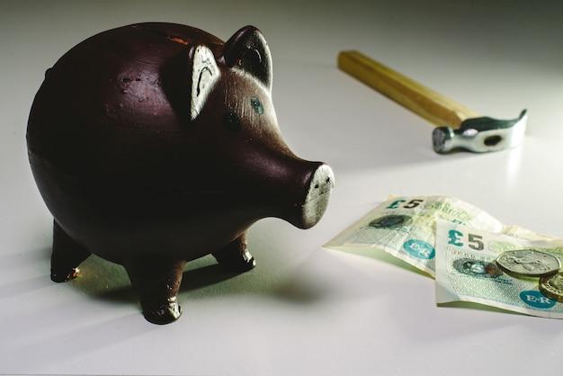 Um sparschwein mit englischem geld zu brechen, um in zeiten der wirtschaftskrise ersparnisse zu erzielen.