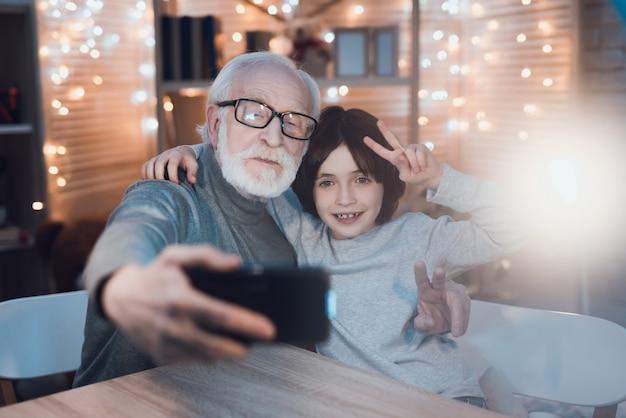 Umarmen des großvaters und des enkels, die selfie machen