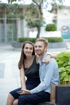 Umarmen eines schönen jungen freundes und einer freundin, die auf einer bank im park sitzen und in die kamera schauen