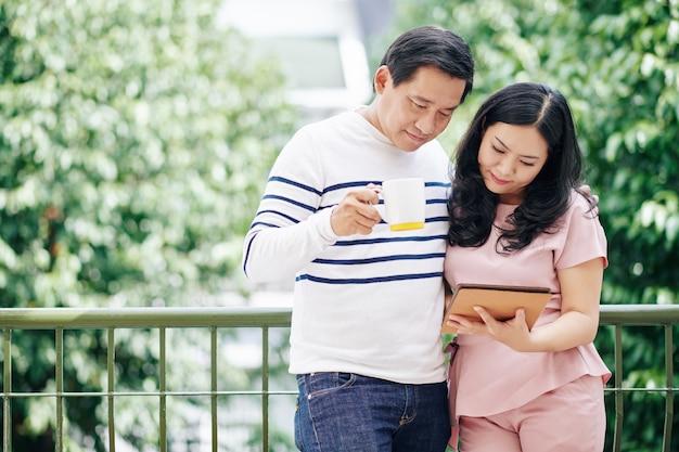 Umarmen reifen asiatischen ehemann und ehefrau, die auf balkon stehen, morgenkaffee trinken und nachrichten auf tablet-computer lesen