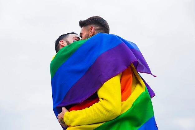 Umarmende gays beim abdecken der regenbogenflagge