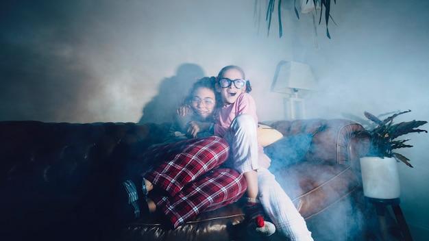 Umarmende teenager, die gruseligen film beobachten