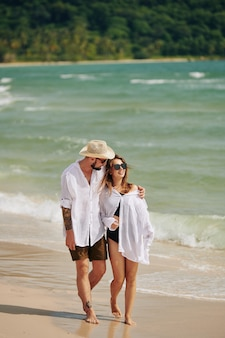 Umarmendes paar, das am strand geht