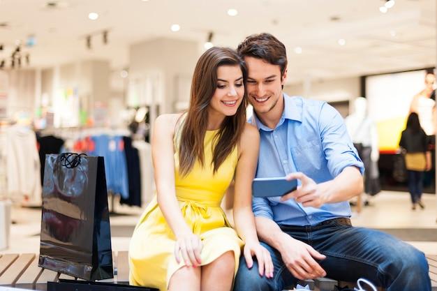 Umarmendes paar, das im einkaufszentrum sitzt und auf handy schaut