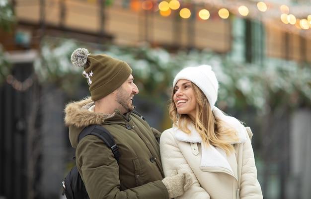 Umarmendes paar, das kamera mit lächeln im winterpark betrachtet.