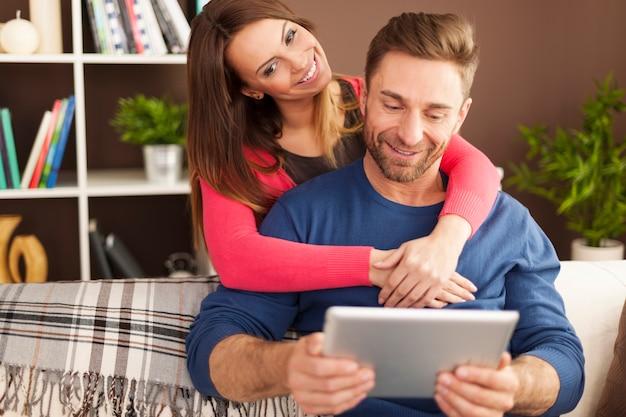 Umarmendes paar mit digitalem tablet im wohnzimmer