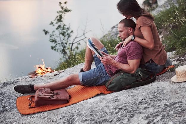 Umarmendes paar mit rucksack, der nahe dem feuer oben auf berg sitzt und aussichtsküste einen fluss oder see genießt.