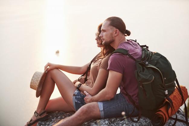 Umarmendes paar mit rucksack, der nahe dem feuer oben auf berg sitzt