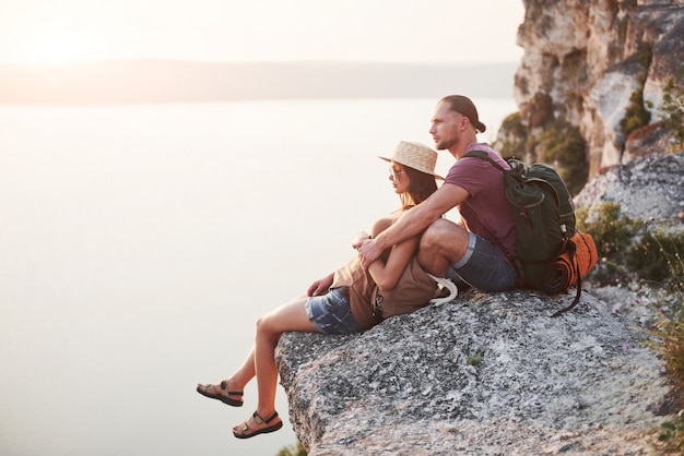 Umarmendes paar mit rucksack, der oben auf felsenberg sitzt und aussichtsküste einen fluss oder see genießt.