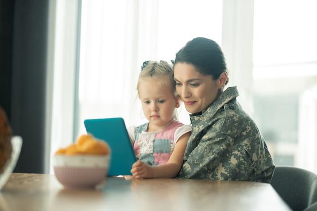 Umarmt ihr kind. frau kehrt nach dem militärdienst nach hause zurück und fühlt sich glücklich, ihr kind zu umarmen