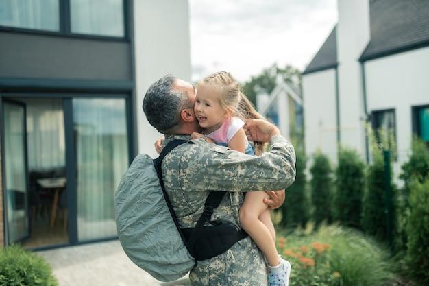 Umarmt seine zarte tochter. militäroffizier in uniform und rucksack umarmt seine zarte tochter