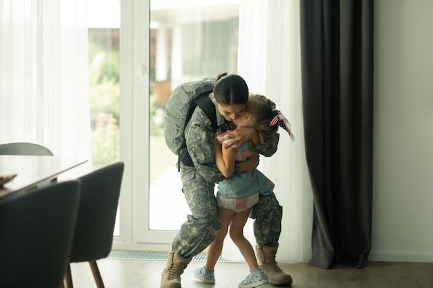 Umarmte tochter. frau in militäruniform und rucksack umarmt ihre tochter
