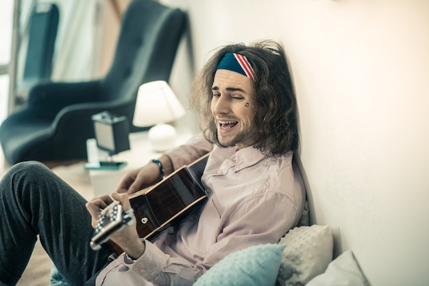 Umarmung der akustikgitarre. seltsamer bärtiger junger musiker grimassen beim ausruhen auf dem bett mit gitarre
