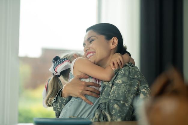 Umarmung der schönen tochter. schöne militärfrau, die lacht, während sie ihre reizende tochter umarmt