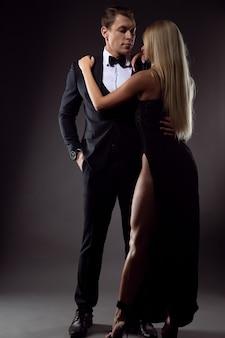 Umarmung einer frau in einem abendkleid und eines mannes in einem eleganten anzug