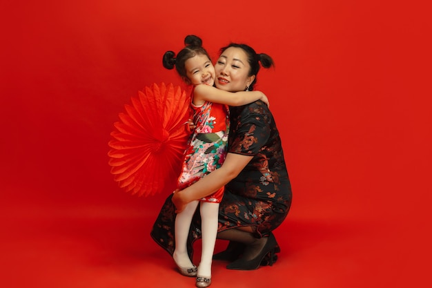 Umarmung, glücklich lächelnd. frohes chinesisches neujahr 2020. asiatisches mutter- und tochterporträt lokalisiert auf rotem hintergrund in traditioneller kleidung. feier, menschliche gefühle, feiertage. copyspace.