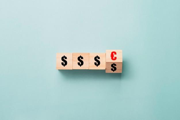 Umdrehen des hölzernen würfelblocks vom dollarzeichen zum eurozeichen auf blauem hintergrund. währungsumtauschkonzept.
