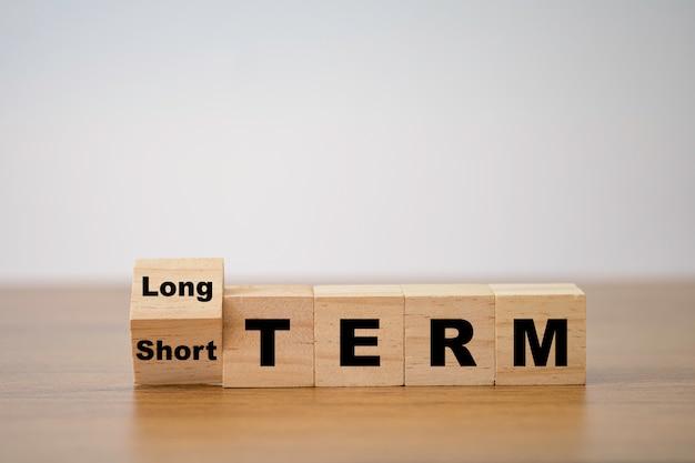 Umdrehen des holzwürfelblocks für den kurzfristigen bis langfristigen wechsel. geschäftsinvestitionskonzept.