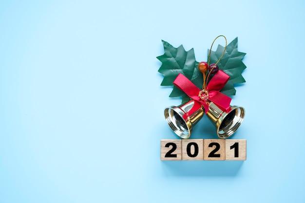 Umdrehen des holzwürfelblocks, um das jahr 2020 bis 2021 mit goldener glocke zu ändern