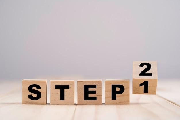 Umdrehen des holzwürfelblocks zum ändern von schritt 1 zu schritt 2 auf dem holztisch.