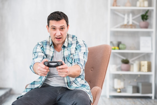 Umfassender kerl, der mit gamepad spielt