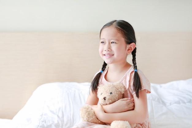 Umfassungs-teddybär des entzückenden kleinen asiatischen mädchens beim auf dem bett zu hause sitzen.