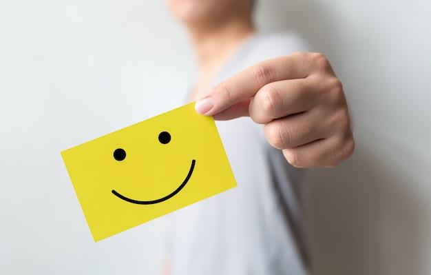 Umfrage zum kundenservice und zur geschäftszufriedenheit. mann, der gelbe karte mit smiley hält