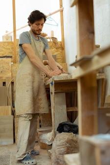 Umgang mit lehm. fleißiger starker kerl mit dunklem bart, der in einer ausgestatteten töpferwerkstatt bleibt und neues material verarbeitet