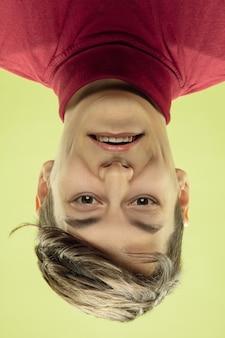 Umgekehrtes porträt des jungen mannes auf gelber studiowand