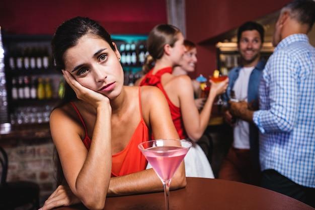 Umgekippte frau, die bei tisch im nachtklub sitzt