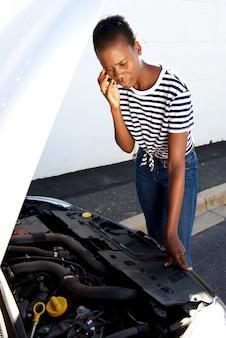 Umgekippte frau, die weg zerlegtes auto auf der seite einer straße rufend um unterstützung bereitsteht