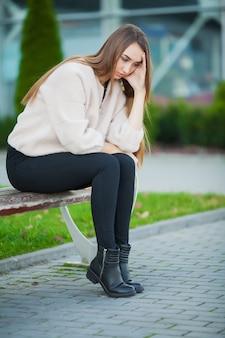 Umgekippte frau mit den problemen, die auf einer bank sitzen